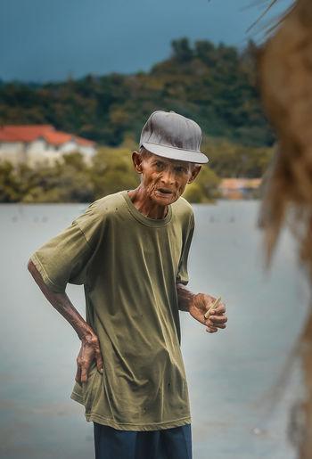 Man wearing hat standing by lake