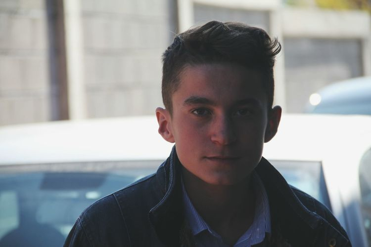 Close-up portrait of young man standing against car