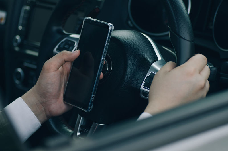 Midsection of businessman using mobile phone while driving car