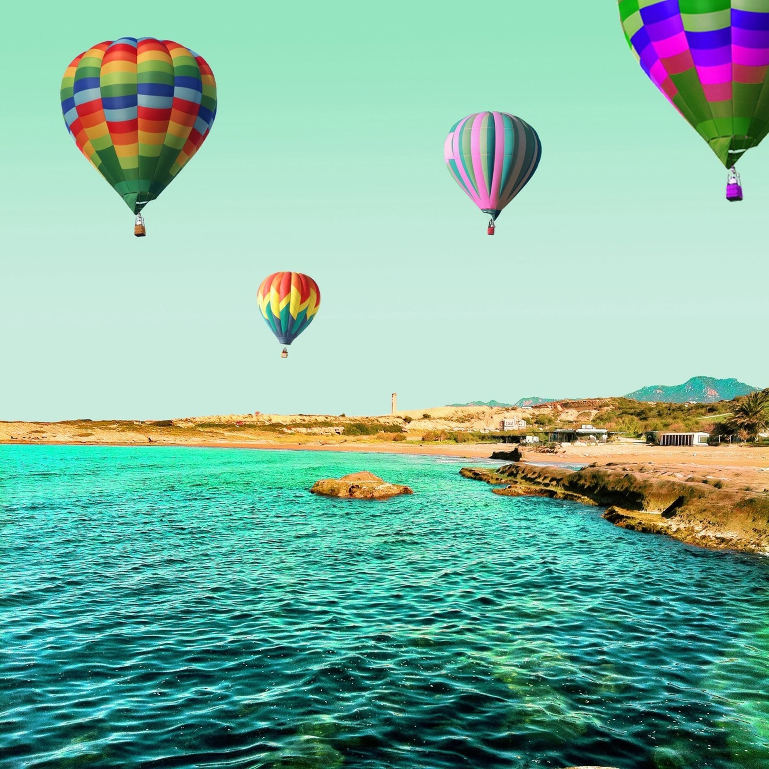 sea, water, parachute, flying, mid-air, multi colored, blue, clear sky, hot air balloon, paragliding, vacations, scenics, tranquility, leisure activity, adventure, tranquil scene, waterfront, beauty in nature, sky, fun