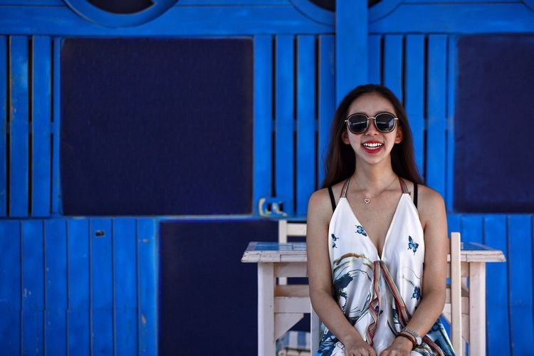 Portrait of smiling young woman standing against blue wall