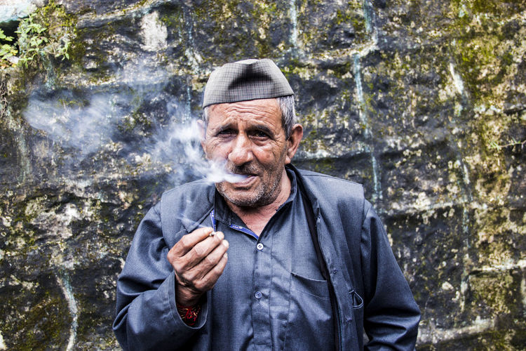 Portrait of senior man smoking bidi against weathered wall
