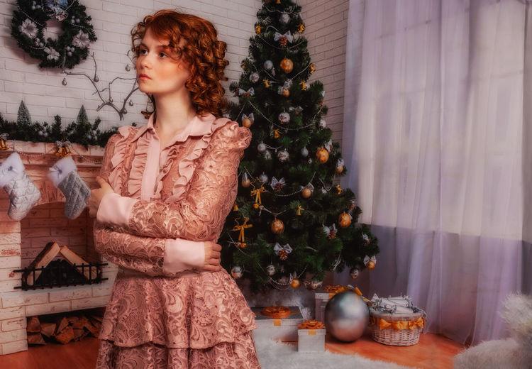 Young woman looking at christmas tree