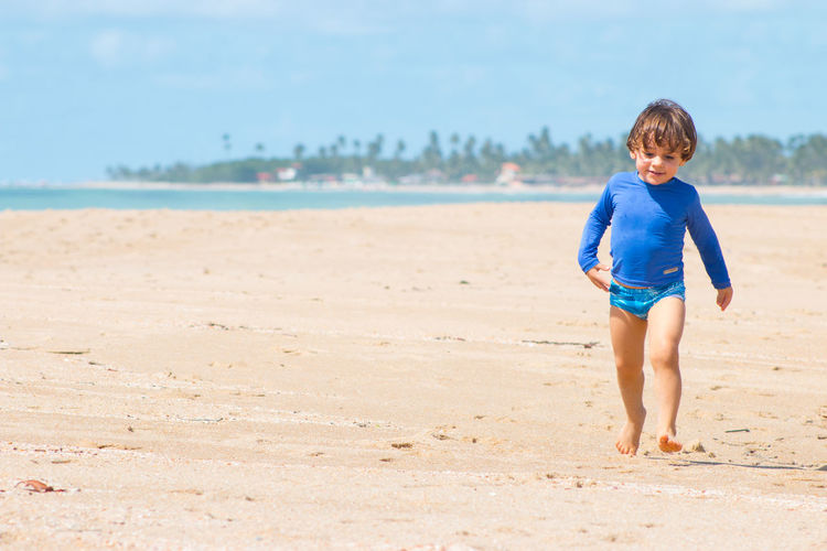 Cute Boy Walking At Beach Against Sky On Sunny Day