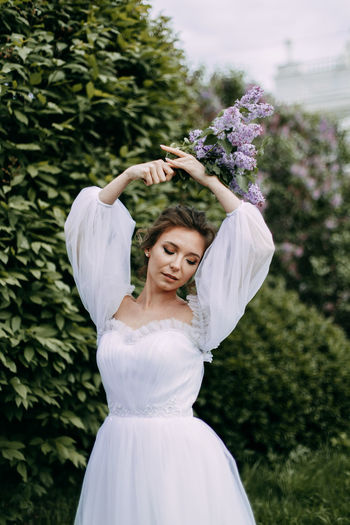 A beautiful delicate elegant young woman bride in a wedding dress walks alone in a blooming park