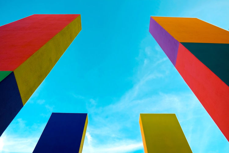 Architecture and urban design with blue sky in the background Blue Day Emotion Flag Low Angle View Multi Colored Nature No People Orange Color Outdoors Patriotism Pattern Pride Red Shape Sky Striped Variation Yellow