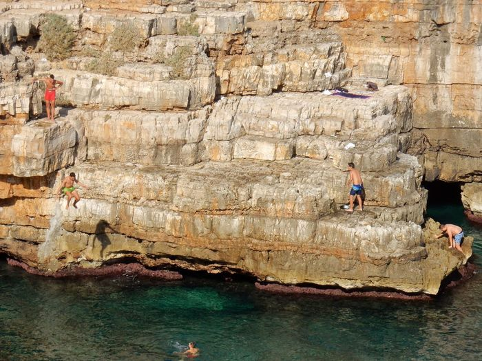 Water Solid Rock Formation Sea Rock - Object Group Of People Rock Nature Real People Adventure Day People Men Land Outdoors Leisure Activity Architecture Lifestyles Waterfront Tuffo Scogliera Pietra Piatta Ragazzi Geological Formation Cala Monachile