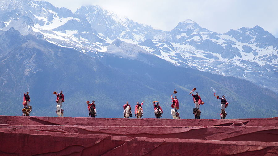 Group of people against snowcapped mountain