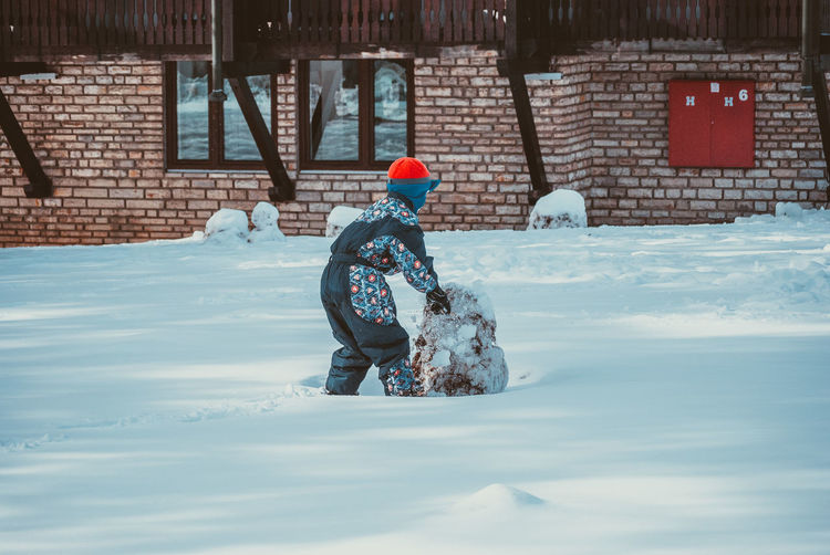Rear view of boy playing on snow covered yard during winter