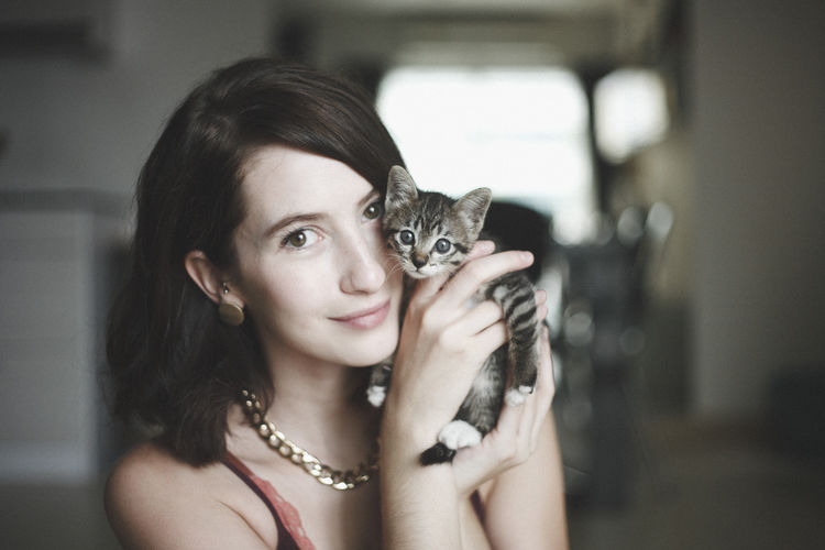 Portrait of beautiful woman holding cute kitten at home