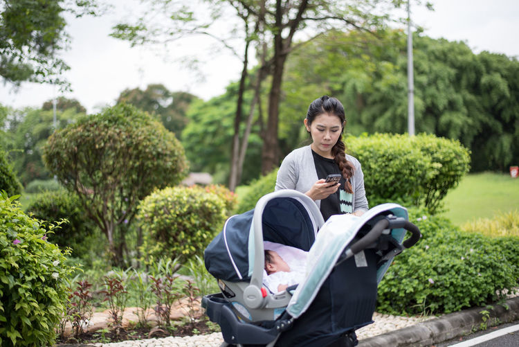 Woman using phone while standing by baby stroller at park