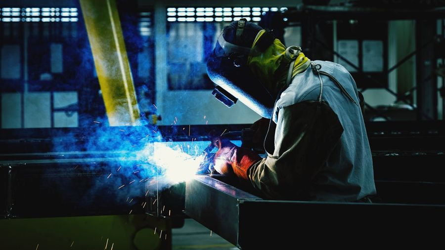 welder welding process FCAW for metal steel.Welding sparks background Metal Industry Steel Worker Working Occupation Technology Men Protective Workwear Occupational Safety And Health Business Finance And Industry Standing Steel Mill Welder Welding Sparks Firework Display Firework - Man Made Object Factory Safety