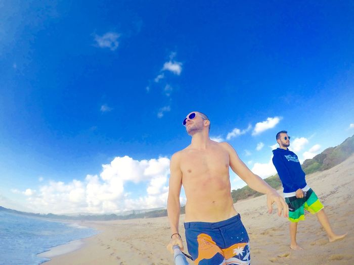Low angle view of young men walking at beach against sky