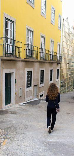 Rear view of woman walking on street by buildings