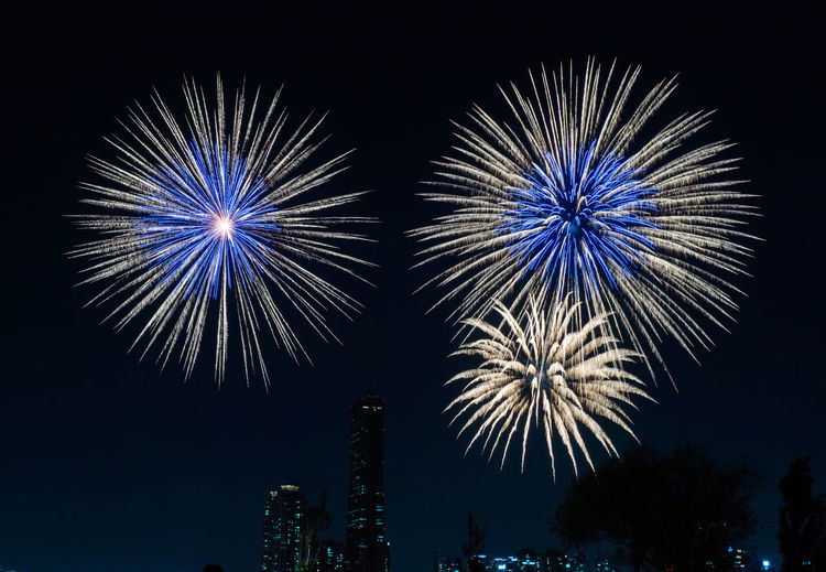 Low angle view of firework display at night in city