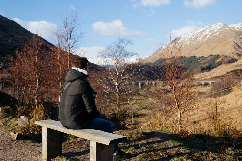 Man Looking At View While Sitting On Bench Against Mountain