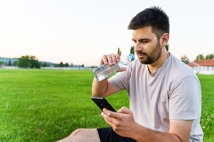 Young man using mobile phone in grass