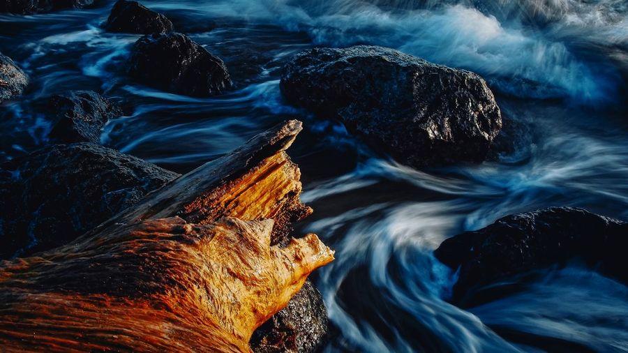High Angle View Of Waves Splashing Rocks In Sea