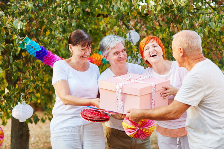 Cheerful Friends Holding Gift While Standing At Park