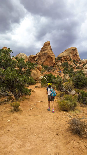 Hiking in the Arches National Park on a beautiful cloudy day Arches National Park, Utah Backpacking Desert Lifestyle Navajo Sandstone Red Rock Trip Woman Adventure Backcountry Beauty In Nature Cloud - Sky Erosion Geooloy Hicking Mountains Journey Lifestyles Nature One Person Outdoors Real People Red Sand Remote Scenics Woman Hiking An Eye For Travel Go Higher Summer Exploratorium
