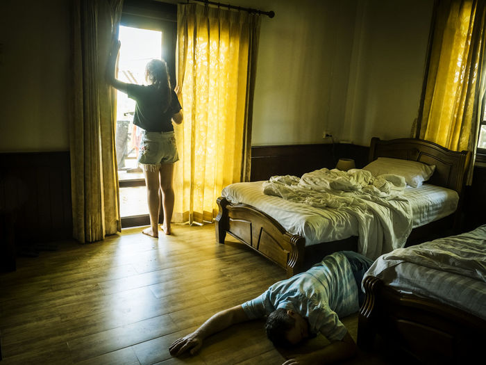 Man lying on floor against girl standing by window at home