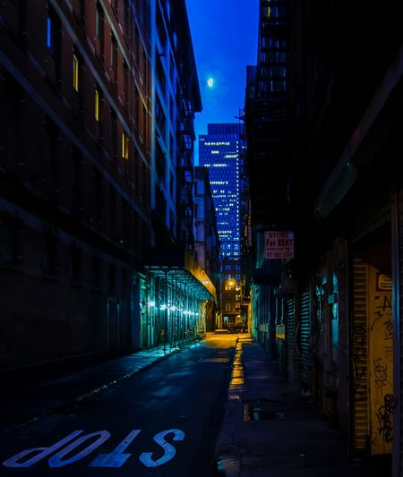 Stop Sign On Street Amidst Buildings In City At Night