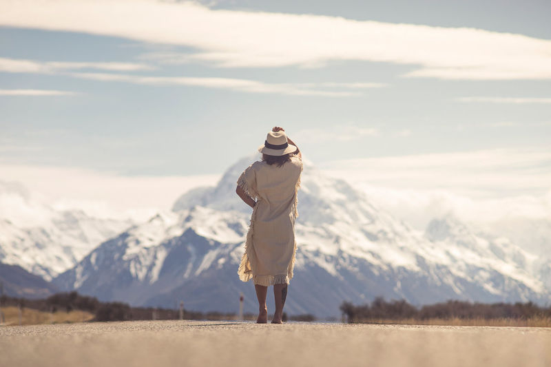 Woman Standing Against Snowcapped Mountains