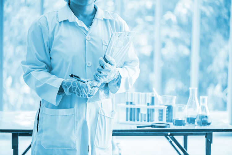 Midsection Of Mid Adult Scientist Standing With Book In Laboratory
