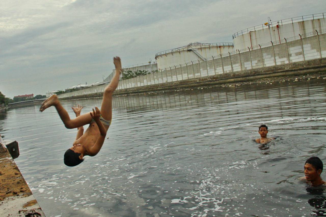water, real people, day, outdoors, leisure activity, enjoyment, mid-air, shirtless, architecture, jumping, sky, lifestyles, full length, togetherness, men, nature, young adult, people