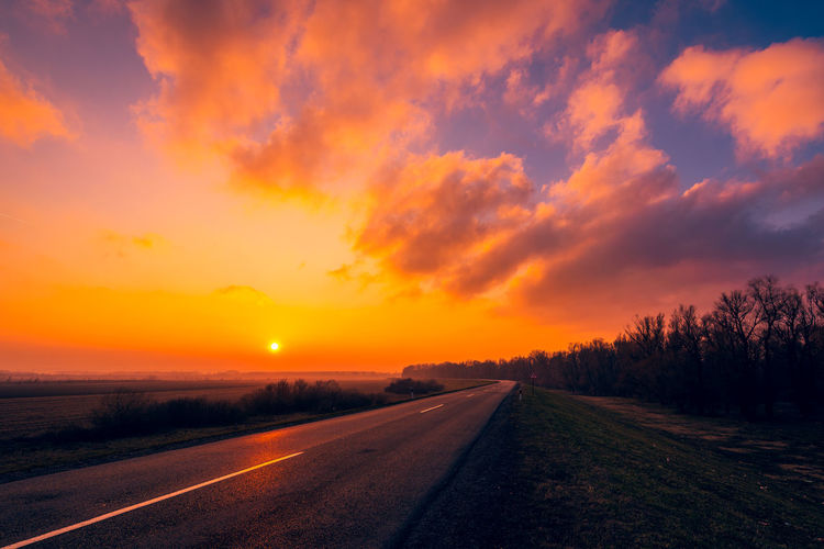 Empty road against sky during sunset