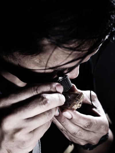 Close-up of man looking at amulet through loupe