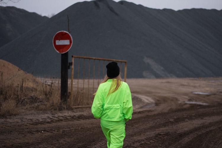 Rear view of woman walking on field against mountain