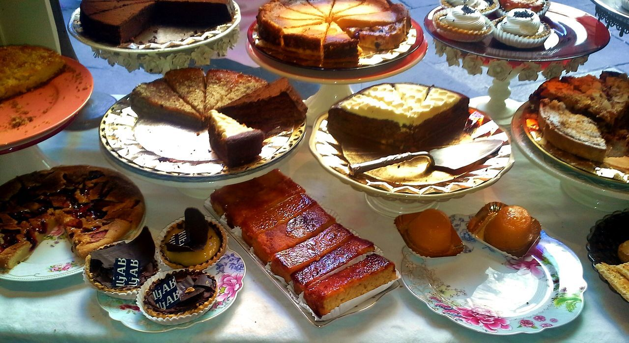 High Angle View Of Various Cakes And Cupcakes On Plates At Home