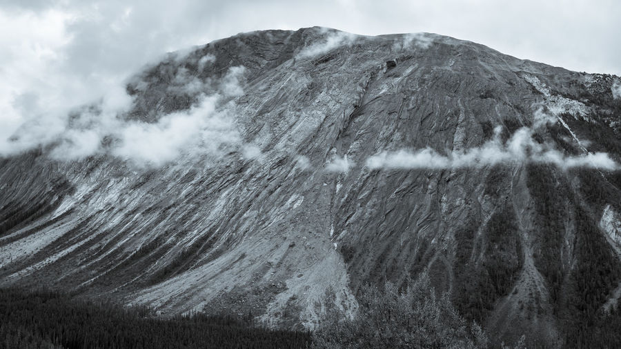 A black and white photo of a rough rocky mountain and fog, banff, canada.