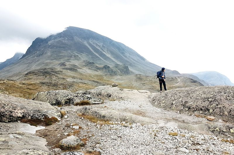 Man standing on landscape against mountains