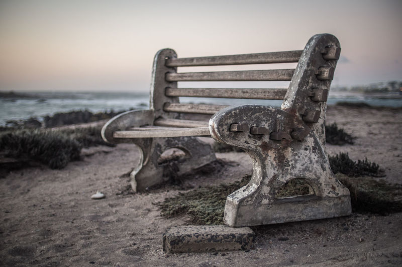 Sky Sea Focus On Foreground No People Water Land Metal Nature Old Beach Rusty Close-up Day Bench Outdoors Abandoned Sand Absence Seat Horizon