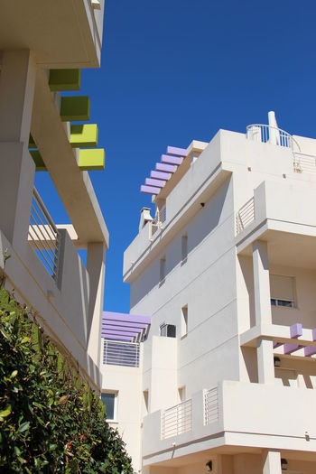 Low angle view of houses against clear blue sky