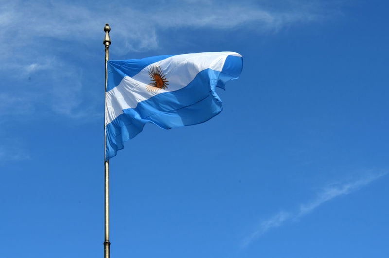 Low angle view of argentinian flag against blue sky