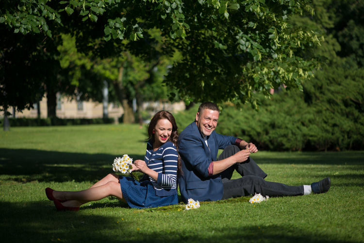 Man with woman sitting on grassy field at park