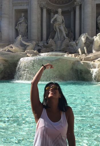 Smiling Young Woman Gesturing Against Trevi Fountain