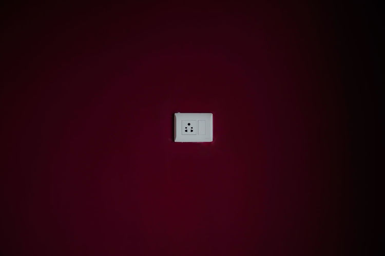 Electrical outlet on maroon wall