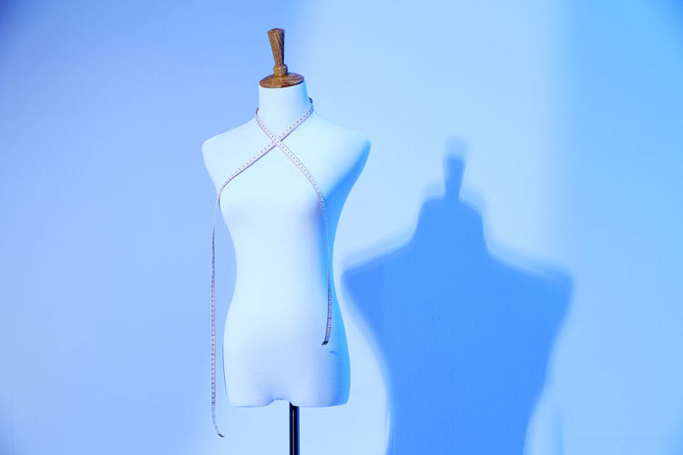 Tape measure on mannequin against wall