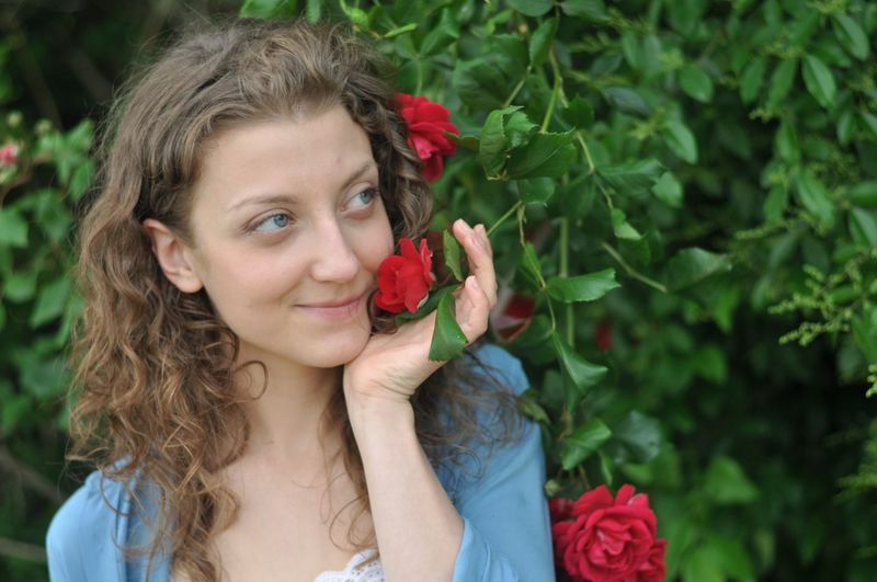 Portrait of smiling young woman holding red rose