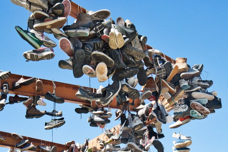 Low angle view of shoes hanging against blue sky