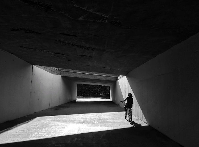 Rear view of woman cycling through underpass