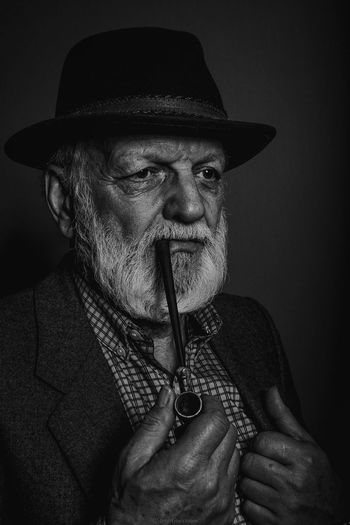 Man Smoking Pipe Cigarette Against Black Background