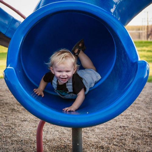 Full Length Of Cheerful Boy Sliding In Blue Slide At Playground