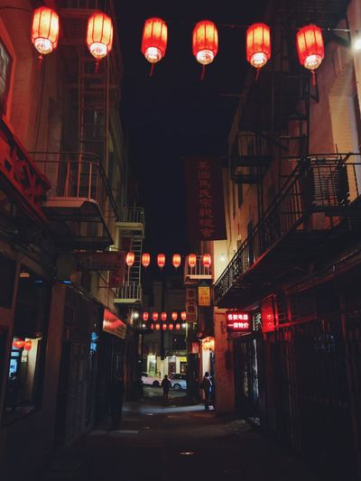 Illuminated lanterns hanging by building at night