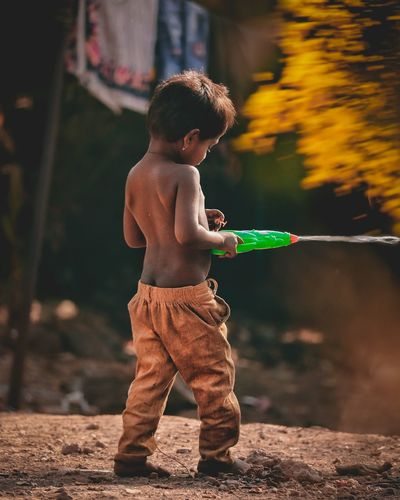 Full length of shirtless boy holding squirt gun while standing on land