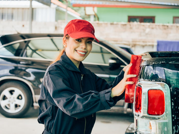Portrait Of Female Mechanic Washing Car